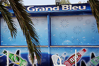 """France. Alpes-Maritimes province.  Antibes. Marineland. A closed shop """" Le Grand Bleu"""" ( in memory of the movie from Luc Besson). Marketing for Perrier and San Pellegrino water bottles. Perrier Fluo (cherry ginger, pepermint) is a soft drink brand. Perrier and competitor San Pellegrino are owned by the Nestlé Corporation. Drawings from various circle of killer whales on the shop window. The killer whale (Orcinus orca), commonly referred to as the orca whale or orca, and less commonly as the blackfish, is a toothed whale belonging to the oceanic dolphin family. Killer whales are regarded as apex predators, lacking natural predators. Marineland is an animal exhibition park and receives more than a million visitors per year. 03.11.06 © 2006 Didier Ruef"""