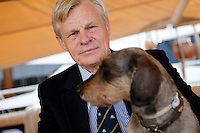 Mikael Krafft, founder and president of Star Clippers, poses for the photographer with his dog Napoleon aboard his yacht Doriana, Hercules port, Monaco, 19th April 2012