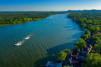 A ski boat with skier in tow passes by the waterfront homes on Lake LBJ in Kingsland, Texas. KINGSLAND, TEXAS. Kingsland is at the juncture of the Llano and Colorado rivers, fifteen miles southeast of Llano in east central Llano County.