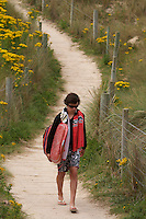 Walking along the boardwalk at Gwithian with a surfboard. Cornwall, July 2008. Pic copyright STeve Behr / Stockfile