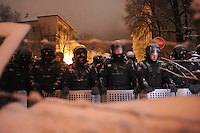 Police forces seen from behind barricades. Tonight the  police is expected to forcedly evacuate the streets from the protesters blocking all the government buildings. Kiev. Ukraine.