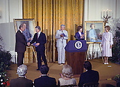 """United States President Jimmy Carter shakes hands with former US President Gerald R. Ford as he and first lady Rosalynn Carter participate in the unveiling ceremony of the portraits of President Ford and former first lady Betty Ford in the East Room of the White House in Washington, DC on August 4, 1980. The paintings will be on permanent display at the White House along with those of other US Presidents and first ladys.  From left to right: President Ford; President Carter; Nash Castro, Vice Chairman, White House Historical Association; first lady Rosalynn Carter; and former first lady Betty Ford.<br /> Credit: Benjamin E. """"Gene"""" Forte / CNP"""