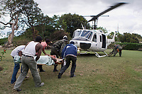 Haitians and MINUSTAH peacekeepers load an injured woman into a helicopter after an earthquake measuring 7 plus on the Richter scale rocked Port au Prince Haiti just before 5 pm yesterday