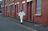 Spraying weeds in an empty and boarded-up street in Salford.