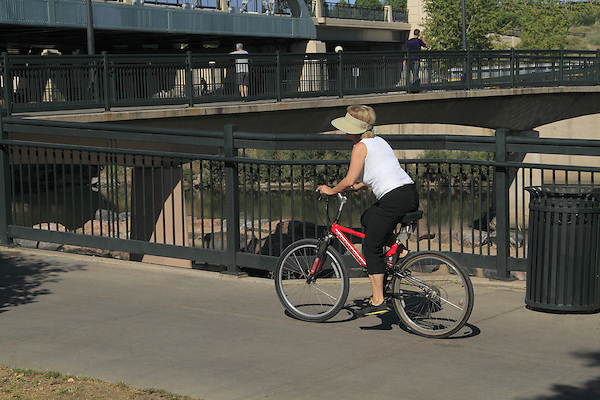 Older woman riding bike on a sidewalk in Denver, Colorado. .  John offers private photo tours in Denver, Boulder and throughout Colorado. Year-round.