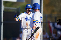South Dakota State Jackrabbits designated hitter Luke Ira (1) high fives Braeden Brown (32) after scoring a run during a game against the Northeastern Huskies on February 23, 2019 at North Charlotte Regional Park in Port Charlotte, Florida.  Northeastern defeated South Dakota State 12-9.  (Mike Janes/Four Seam Images)