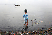 "A young boy looks out onto Jakarta Bay as a fishing boat passes by. According to the Climate Reality Project, ""without flood protection measures, sea level rise could expose up to 6 million Indonesians to annual coastal flooding. The worst of the flooding would occur on the island of Java, where Jakarta is located."""