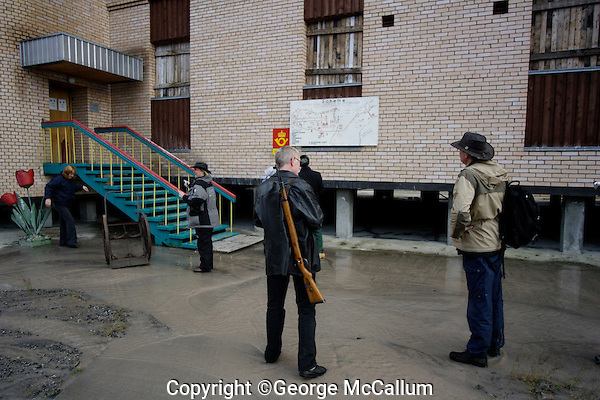 Ecotourists visiting Pyramiden abandoned Russian mining town on Spitzbergen.Guide must carry a weapon as protection from Polar bears. Arctic Norway