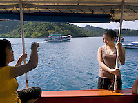Thailand. Trat province. Diving boat on the way in Ko Rang island. Two thai young women, both tourists, take pictures from each other while standing on the upper deck. Blue sky and clouds. Ko Rang island is a natural park. 13.04.09 © 2009 Didier Ruef