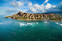An aerial shot of Diamond Head at sunrise, with waves rushing towards the beach and surfers waiting for waves in the ocean.