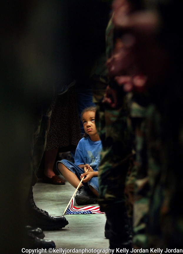 Rickey Moore Jr. sits on the floor holding his American Flag looking up at a long line of National Guard troops looking for his father Sgt. Rickey Moore, of Port Orange,  during a deployment ceremony for the soldiers at the Daytona Beach International Airport Tuesday morning, March 18, 2003 in Daytona Beach. Rickey may be away from his father for up to a year as he is deployed for the possible war with Iraq.(Kelly Jordan)..**FOR DEPLOYMENT GALLERY**