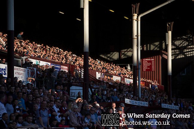 Heart of Midlothian 1 Birkirkara 2, 21/07/2016. Tynecastle Park, UEFA Europa League 2nd qualifying round. Home supporters bathed in evening sunlight in the historic main stand at Tynecastle Park, Edinburgh watching the first-half action as Heart of Midlothian played Birkirkara of Malta in a UEFA Europa League 2nd qualifying round, second leg. The match ended in victory for the Maltese side by 2-1 and they progressed on aggregate after the first match had ended 0-0. The game was watched by 14301 spectators, including 56 visiting fans of Birkirkara. Photo by Colin McPherson.