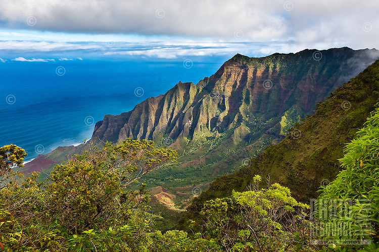A glimpse of the Na Pali Coast from the Kalalau Lookout on a bright sunny day in Kaua'i.