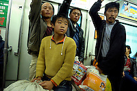 Newly arrived migrants (a youth and three adults) from the countryside, riding with their belongings in sacks on the Beijing metro in Beijing, China. China faces huge job pressures with 12 million urban dwellers expected to be out of work and an army of rural workers crowding into cities with the bleak forecast based on estimates that 24 million people, or more than the entire population of Australia, will enter the job market in 2007..01 Nov 2006
