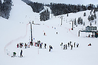 Skiiers and snowboarders gather near the base of the hill at the bunny hill at Showdown Ski Area on King's Hill in the Little Belt Mountains near Neihart, Montana, USA.