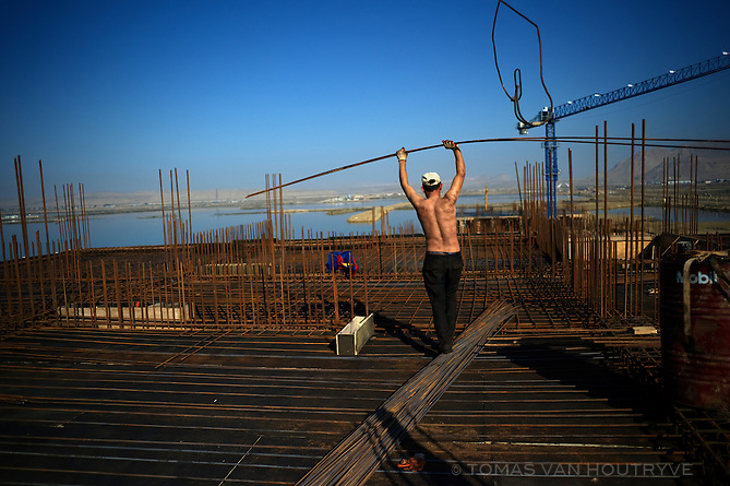A worker balances while holding steel reinforcing bars on top of a building under construction on Kazar Islands in the region Qaradagh, Azerbaijan. Kazar is a massive artificial island project, following the spirit of man-made islands in Qatar.