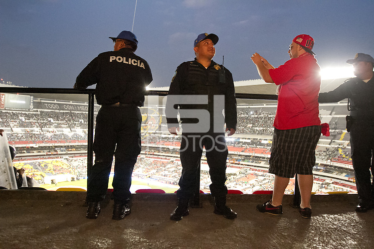 A USA fan takes photos from the American supporters section protected by Mexican police at Azteca stadium before the USA vs. Mexico World Cup Qualifier in Mexico City, Mexico on March 26, 2013.
