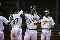 AZL Athletics right fielder Danny Bautista (20) is congratulated by teammates after scoring a run during an Arizona League game against the AZL Giants Orange at Lew Wolff Training Complex on June 25, 2018 in Mesa, Arizona. AZL Giants Orange defeated the AZL Athletics 7-5. (Zachary Lucy/Four Seam Images)