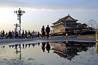 Couple at dusk on Tiananmen Square, walking past Tiananmen Gate, the entry to the Forbidden City, reflected in puddle from melting snow..