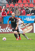 Toronto, Ontario - May 3, 2014: Toronto FC midfielder Michael Bradley #4 and New England Revolution midfielder Andy Dorman #12 in action during a game between the New England Revolution and Toronto FC at BMO Field.<br /> The New England Revolution won 2-1.