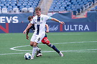 FOXBOROUGH, MA - JULY 4: Aaron Walker #8 of Greenville Triumph SC passes the ball under pressure from Tyler Freitas #54 of the New England Revolution II during a game between Greenville Triumph SC and New England Revolution II at Gillette Stadium on July 4, 2021 in Foxborough, Massachusetts.