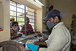 Government worker at emergency duty at a government controlled ration shop while customers peep through the window in New Garia during 21 days lock down in India due to covid 19 pandemic. Kolkata, West Bengal, India. Arindam Mukherjee.