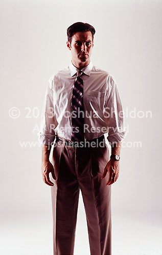 Dramatically lit man wearing business attire on white seamless<br />