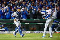 Chicago Cubs pitcher Aroldis Chapman (54) catches last out game ball from Willson Contreras (40) after closing out Game 5 of the Major League Baseball World Series against the Cleveland Indians on October 30, 2016 at Wrigley Field in Chicago, Illinois.  (Mike Janes/Four Seam Images)