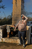 """Charleston, South Carolina<br /> October 26, 2013<br /> <br /> Matthew Matheson, who goes by """"Matty Death Bro"""" on social media due in part to the heart attack he suffered in his mid-20's downs a beer as the chefs burn off the excess barbecued pig heads. <br /> <br /> Internationally renowned chefs, attending the Cook It Raw.barbecue at Bowens Island."""