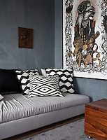 Geometric patterned cushions provide a comfy place to relax in the sitting room, whilst vines creep around a wolf in sheep's clothing on the wall