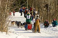 Butch Austin runs past spectators on bike trail in Anchorage at the ceremonial start day of Iditarod Alaska