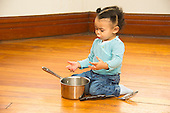 MR / Schenectady, NY. Toddler (1 African-American and Caucasian) babbles while using a pot and spoons as toys to play. MR: Dal4. ID: AM-HD. © Ellen B. Senisi