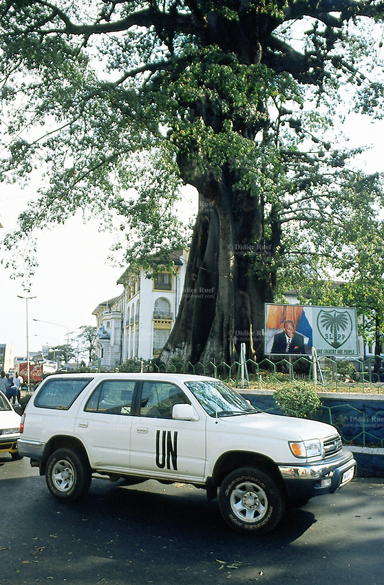 Sierra Leone. Freetown. An UNAMSIL (United Nations Mission in Sierra Leone) toyota landcruiser passes early morning in the town center near a poster of the newly elected president of Sierra leone, Mr Ahmad Tejan Kabbah.© 2002 Didier Ruef