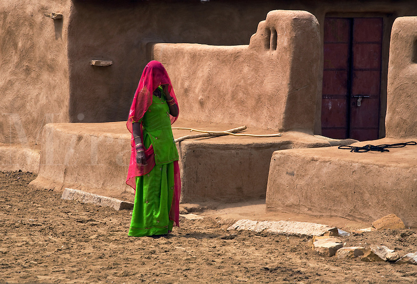 A BANJARI TRIBAL WOMAN and her classic MUD HOUSE in a village in the THAR DESERT near JAISALMER - RAJASTHAN, INDIA