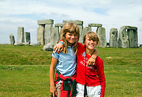 Two hugging and happy young girls in front of Stonehenge monument, England, Great Britian