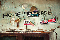"""Nigeria. Enugu State. Agbani. Above the entrance to a private house. Light bulb. A crucifix with Jesus Christ and religious stickers on the wall. """"God has answered us. Amen"""""""" My Father, My Fighter. Exodus 14.14"""" (The Lord will fight for you; you need only to be still.). A sticker is a type of label: a piece of printed paper, plastic, vinyl, or other material with pressure sensitive adhesive on one side. They can be used for decoration or for functional purposes, such as religious situation. 9.07.19 © 2019 Didier Ruef"""