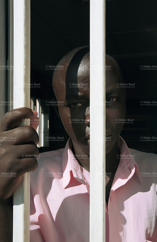 Rwanda. Southern province. District of Muhanga. Central jail of Gitarama. Minors block. A black teenager boy, wearing the pink prisoner's clothes stands in the classroom behind a barred window. Behind bars. Minors in detention behind bars. Detention pending trial and after trial, when sentenced to prison. The non-governmental organization (NGO) Fondation DiDé - Dignité en détention runs the Encademi (Encadrement des mineurs) program. Prison centrale de Gitarama. Quartier des mineurs.  © 2007 Didier Ruef