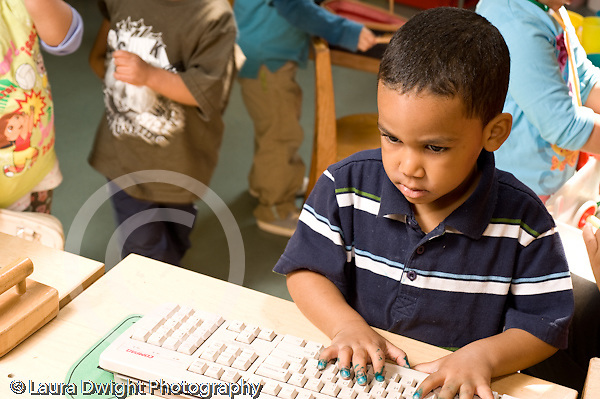 Education Preschool 3-4 year olds pretend play boy typing on computer keyboard in kitchen family area horizontal