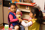 Day Care Center 3 year olds two girls playing in dressup pretend play area one offering the other one a pacifier for her doll, talking