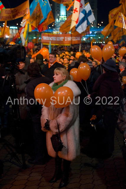 """Kiev, Ukraine.December 28, 2004..A pro-Viktor Yushchenko rally in Kiev as election polls show him as a clear winner however he has not yet been declared the winner nor has his opponent refuses to admit defeat. He is joined on stage by his wife Kathy, two children as well as his political partner Yulia Timoshenko. ..Supporters rally to support Yushchenko on Maidan Independence Square.  ..The first round of voting was considered fraudulent when the ruling president Viktor Yahukovich won and the opposition candidate Viktor Yushchenko lost. ..Several hundred  thousand Ukrainians took to the streets of Kiev and held daily rallies on Maidan Independence Square. The protests lasted nearly a month before the first vote was declared invalid and a new round of elections held on December 26, 2004. ..The demonstrations would come to be known as the """"Orange Revolution"""" after the color of the opposition party."""