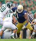 Sept. 21, 2013; Michigan State Spartans running back Nick Hill (20) runs into the waiting defense of Louis Nix.