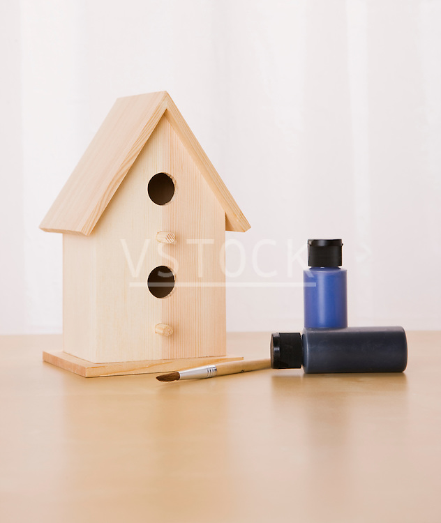 Wooden birdhouse with paints and paintbrush
