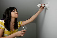 Montreal (Qc) CANADA, July 24, 2007 - Model Released photo- A young asian woman replace an incandescent light bulb by an efficient compact fluorescent light bulb.(CFL)<br /> <br /> A compact fluorescent lamp (CFL), also known as a compact fluorescent light bulb is a type of fluorescent lamp designed to replace an incandescent lamp. Many CFLs can fit in the existing incandescent light fixtures.<br /> <br /> Compared to incandescent lamps of the same luminous flux, CFLs use less energy and have a longer rated life. In the United States, a CFL can save over US$30 in electricity costs over the lampÕs lifetime compared to an incandescent lamp and save 2000 times their own weight in greenhouse gases[<br /> <br /> photo : (c) images Distribution