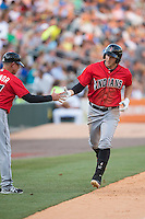 Brent Morel (5) of the Indianapolis Indians slaps hands with third base coach Dean Treanor (27) after hitting a home run against the Charlotte Knights at BB&T BallPark on June 20, 2015 in Charlotte, North Carolina.  The Knights defeated the Indians 6-5 in 12 innings.  (Brian Westerholt/Four Seam Images)