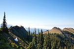 View northwest from Blue Mountain above Deer Park, highlights razor back peaks and looks over the Strait of Juan de Fuca toward the Pacific Ocean.  Two hikers on ledge are dwarfed by the expanse.  Olymppic National Park.  Olympic Penninsula, Washington.  Outdoor Adventure. Olympic Peninsula