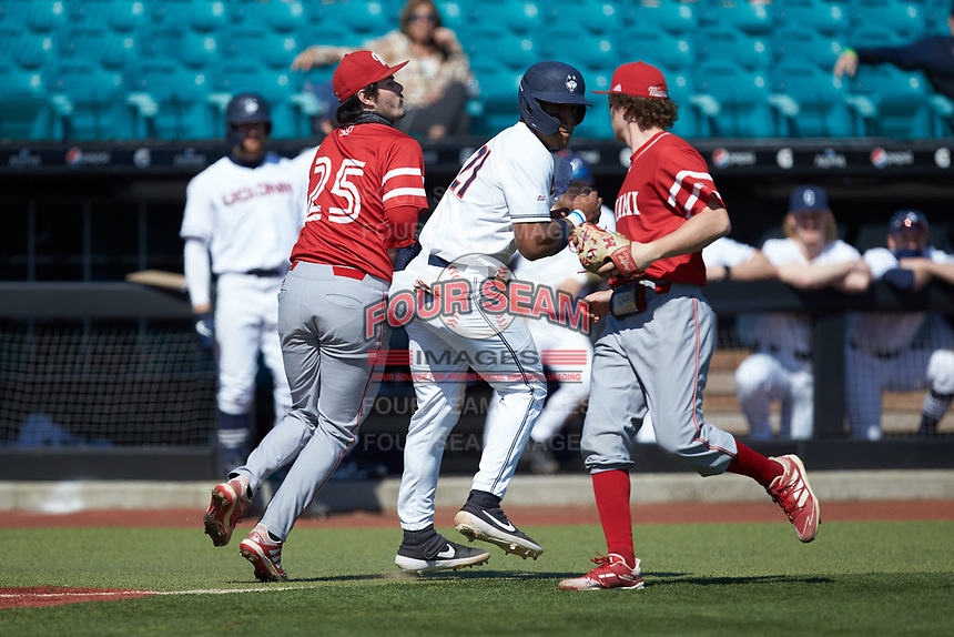 Reggie Crawford (21) of the Connecticut Huskies is tagged out by Grant Hartwig (25) of the Miami Redhawks after being caught in a run-down between third base and home plate at Springs Brooks Stadium on March 5, 2021 in Conway, South Carolina. The Huskies defeated the Redhawks 5-0. (Brian Westerholt/Four Seam Images)