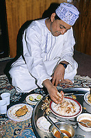 Nizwa, Oman, Arabian Peninsula, Middle East - Omani Man Eating Lunch of Fish, White Rice, and Sauce.  Meals are frequently eaten while sitting on the floor, and are still often eaten by hand.