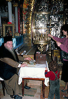 This is a priest of the Russian Orthodox church inside the Church of the Holy Sepulcher or of All Nations, where Jesus was buried after His crucifixion. There are several churches of different religions built inside the enormous Church of the Holy Se pulc