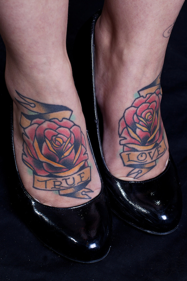 Young danish woman with pinup girl on left shoulder and left lower arm, swallows on left and right front. Two roses on feet with the words True Love.<br /> From the Kolding Tattoo Convention, Denmark