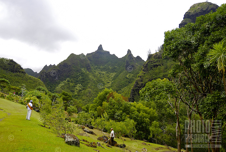 Two tourists stand on the gently sloping green grounds at Limahuli Gardens, on Kauai's majestic north shore. One of the 5 National Tropical Botanical gardens in the US.